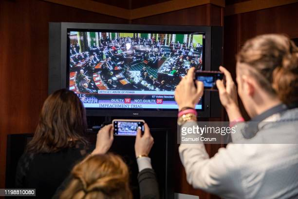 Reporters take photos of the television as they watch the Senate vote on whether or not to acquit President Donald Trump on the two articles of...