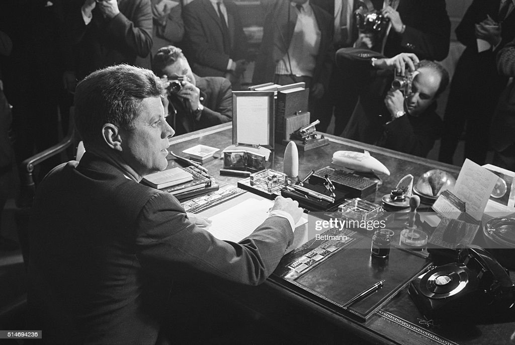 Reporters take pictures of President Kennedy behind his desk, after signing the arms embargo against Cuba. The embargo effectively quarantined Cuba.