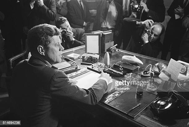 Reporters take pictures of President Kennedy behind his desk after signing the arms embargo against Cuba The embargo effectively quarantined Cuba