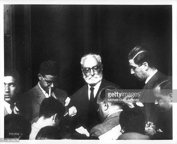 Reporters with pen and paper surround man in a scene from the film 'To Die in Madrid' aka 'Mourir a Madrid' 1965