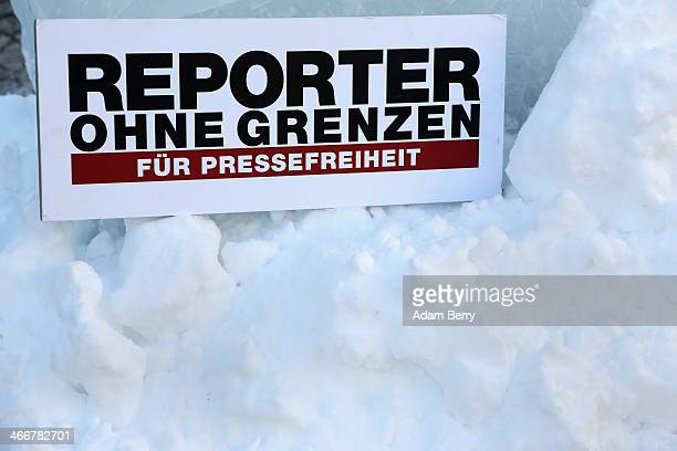 Reporters Without Borders sign sits in the snow below an ice sculpture featuring a poster with a burning newspaper shaped like an Olympic torch and...