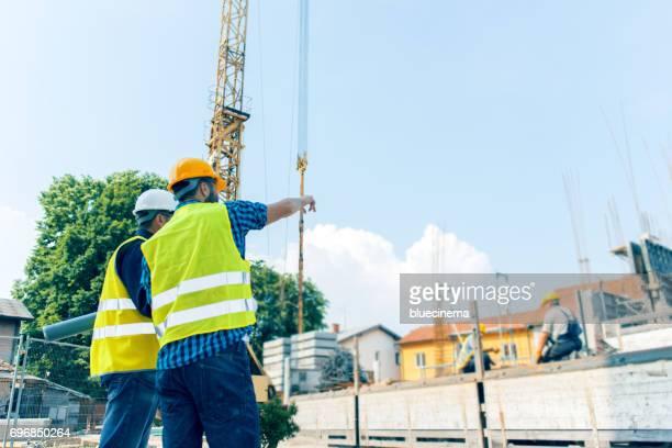 rapportage aan aannemer op bouwplaats - wijzen handgebaar stockfoto's en -beelden