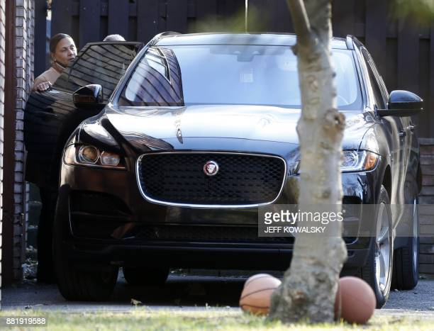 US Reprepesentative John Conyers Democrat of Michigan is helped by an unidetified person into a vehicle outside his house on November 29 2017 in...