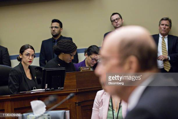 Representative Alexandria OcasioCortez a Democrat from New York left listens during a House Oversight Committee hearing with Wilbur Ross US commerce...