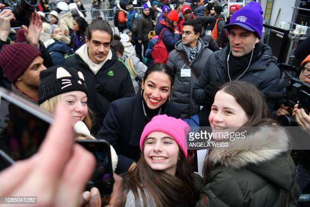 US Representative Alexandria OcasioCortez poses for a photo with marchers as she attends the Women's March in New York on January 19 2019