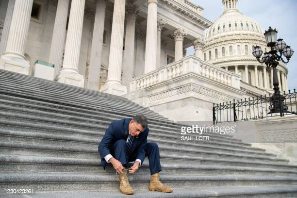 Representative Andrew Clyde, Republican of Georgia, ties his combat boots following a photograph with first-term Republican members of Congress on...