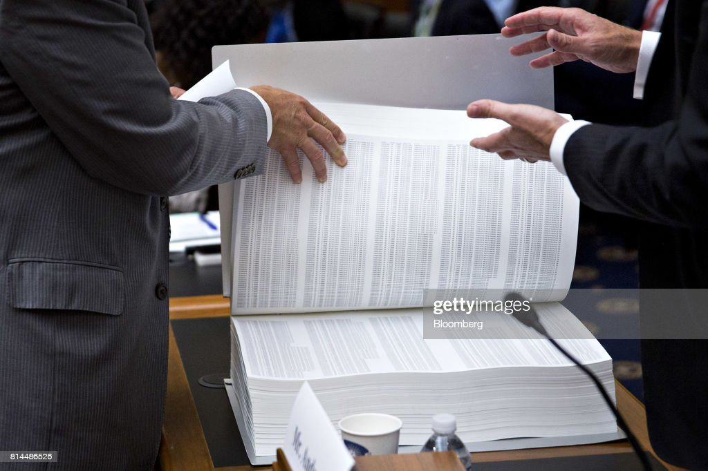 Representative Bill Huizenga, a Republican from Michigan and chairman of the House Capital Markets, Securities, and Investment Subcommittee, left, and Matthew Andresen, founder and co-chief executive officer of Headlands Technologies LLC, right, look over a Headlands' municipal bond issuers binder before the start of a subcommittee hearing in Washington, D.C., U.S., on Friday, July 14, 2017. The hearing is entitled A Review of Fixed Income Market Structure. Photographer: Andrew Harrer/Bloomberg via Getty Images