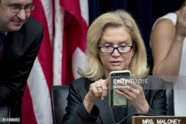 Representative Carolyn Maloney a Democrat from New York looks at her mobile phone before the start of a House Financial Services Subcommittee hearing...