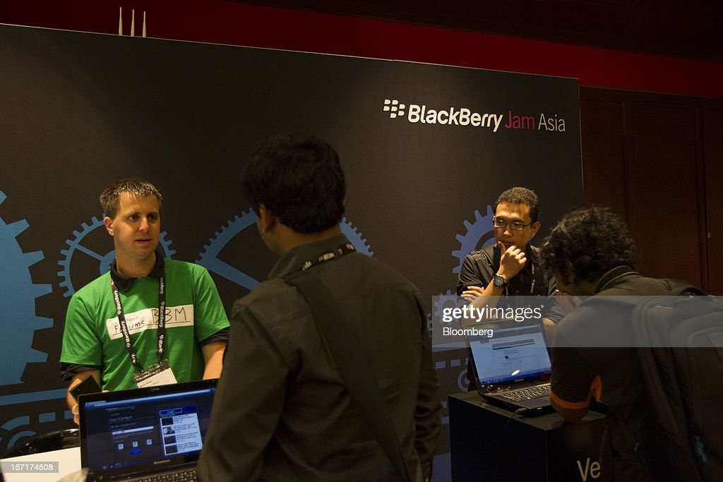 A representative for Research In Motion Ltd. (RIM) speaks with an attendee at the BlackBerry Jam Asia developer conference in Bangkok, Thailand, on Thursday, Nov. 29, 2012. RIM gained after Goldman Sachs Group Inc. upgraded the stock to buy, saying the new BlackBerry 10 phones could help it return to profitability in fiscal 2014. Photographer: Brent Lewin/Bloomberg via Getty Images
