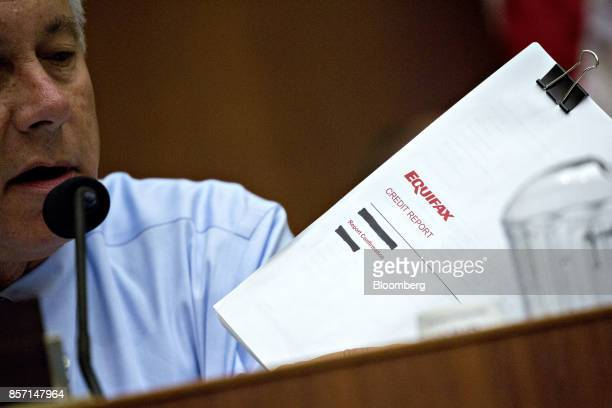Representative Fred Upton a Republican from Michigan holds an Equifax credit report while questions Richard Smith former chairman and chief executive...