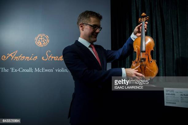 A representative from Sotheby's Hong Kong holds a rare 1684 violin by Antonio Stradivari to the press during a media preview in Hong Kong on February...