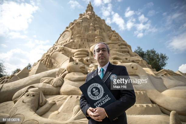 A representative from the Guinness Book of World Records Jack Brockba looks at his notes next to the Sandburg sandcastle on September 1 2017 in...