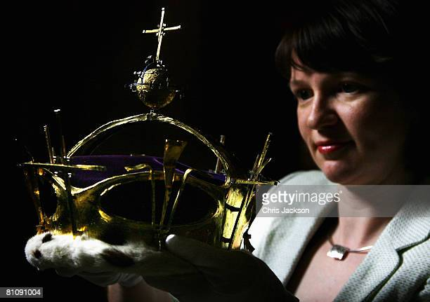 A representative from Windsor Castle holds up The Prince of Wales' investiture coronet at an exhibition to celebrate his 60th Birthday in Windsor...
