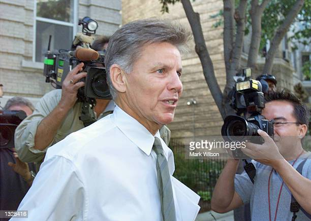 Representative Gary Condit is surrounded by news photographers as he leaves his apartment building July 12, 2001 in Washington, DC. Major daily...