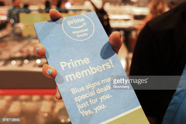 A representative holds pamphlets about special deals offered to Amazoncom Inc Prime members during the grand opening of a Whole Foods Market Inc...