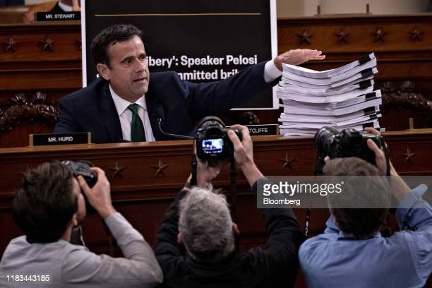 Representative John Ratcliffe a Republican from Texas displays a stack of sworn testimony while questioning witnesses during a House Intelligence...