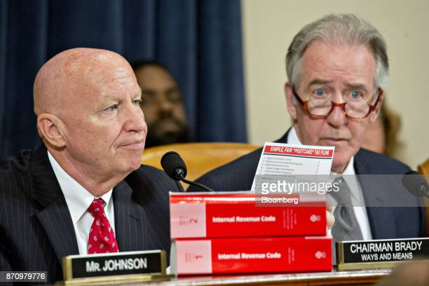 Representative Kevin Brady a Republican from Texas and chairman of the House Ways and Means Committee left holds up a Simple Fair 'Postcard' Tax...