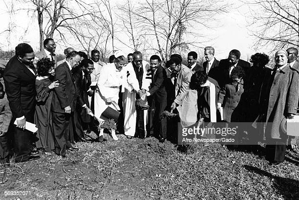 Representative Kweisi Mfume and Councilman Nathaniel J McFadden gathering outside with a group of church goers including a priest 1987