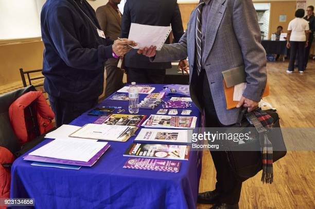 A representative left review the resume of a job seeker during a Shades of Commerce Career Fair in the Brooklyn borough of New York US on Saturday...