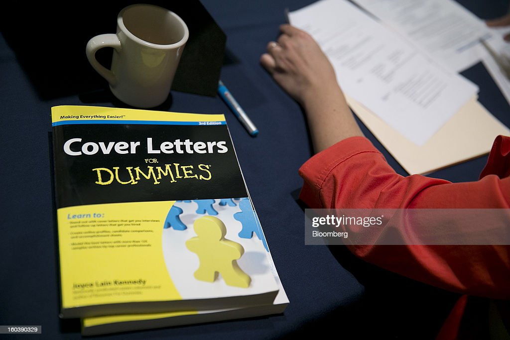 A representative looks over a job seeker's resume at a National Career Fairs job fair in Arlington, Virginia, U.S., on Wednesday, Jan. 30, 2013. The U.S. Labor Department is scheduled to release initial jobless claims data on Jan. 31. Photographer: Andrew Harrer/Bloomberg via Getty Images