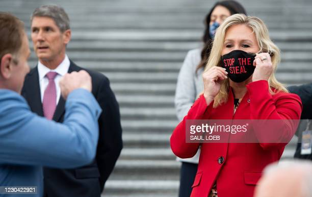 "Representative Marjorie Taylor Greene, Republican of Georgia, holds up a ""Stop the Steal"" mask while speaking with fellow first-term Republican..."