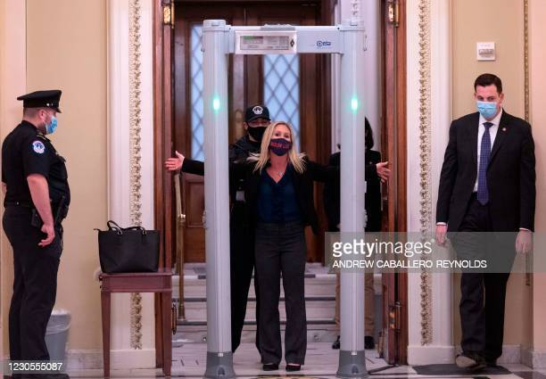 Representative Marjorie Taylor Greene spreads out her arms as she goes through security outside the House Chamber at Capitol Hill in Washington, DC...
