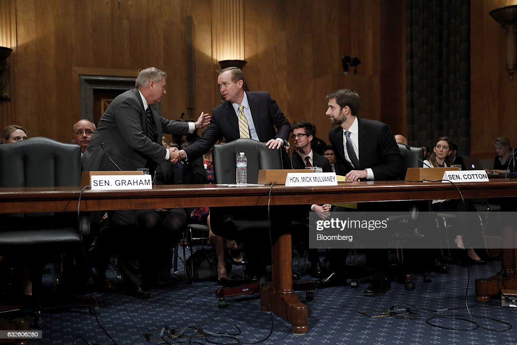 Representative Mick Mulvaney, a Republican from South Carolina and Office of Management and Budget director nominee for U.S. President Donald Trump, center, greets Senator Lindsey Graham, a Republican from South Carolina, left, as Senator Tom Cotton, a Republican from Arkansas, smiles during a Senate Governmental Affairs Committee confirmation hearing in Washington, D.C., U.S., on Tuesday, Jan. 24, 2017. Mulvaney said Tuesday the nearly $20 trillion national debt needs to be 'addressed sooner rather than later' and that he would push Trump to break his campaign promises and cut Social Security and Medicare. Photographer: Aaron P. Bernstein/Bloomberg via Getty Images