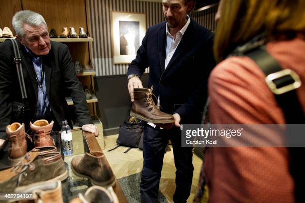 A representative of the label Marc O'Polo explains to participants the materials of shoes at the Marc O'Polo brand stand at the Bread and Butter...