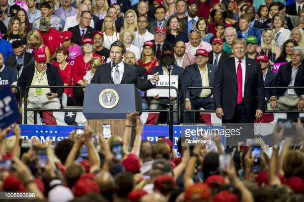 Representative Ron DeSantis a Republican from Florida center left addresses the crowd as US President Donald Trump right smiles onstage during a...