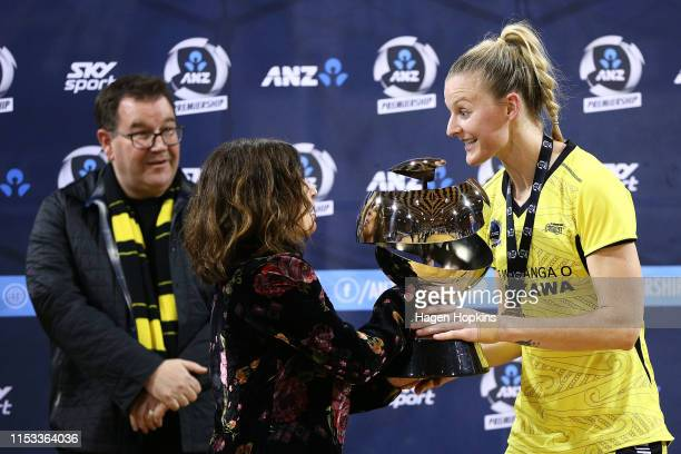 Representative Sarina Pratley hands the ANZ Premiership trophy to Katrina Rore of the Pulse during the ANZ Premiership Netball Final between the...