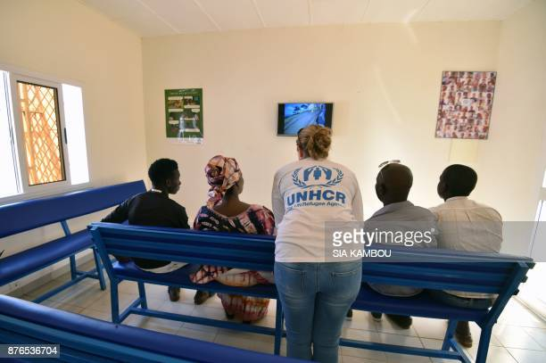 A UNHCR representative speaks with refugees as they watch television in a UNHCR building in Niamey on November 17 after being evacuated from Libya...