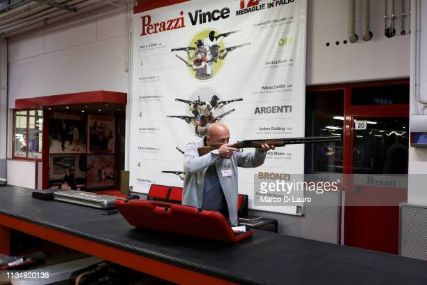 A representative takes aim with a customer's rifle on April 4 2019 at the Perazzi Armi factory in Botticino Mattina a village in the outskirt of the...