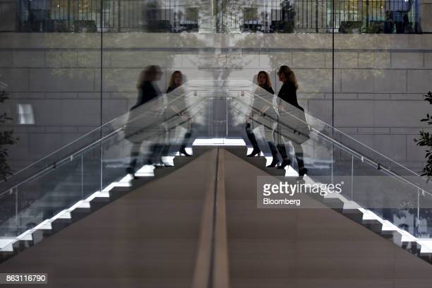 Representatives are reflected in a mirrored wall while climbing a staircase during a media preview of the new Apple Inc Michigan Avenue store in...