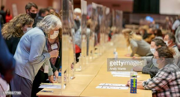 Representatives for President Donald Trump, left, looks over a ballots during the presidential recount vote for Dane County on November 20, 2020 in...