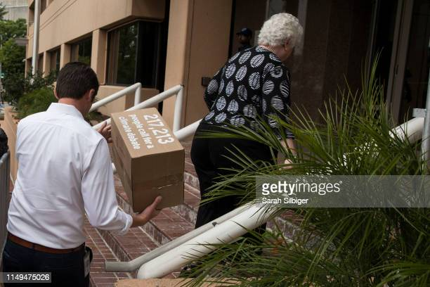 Representatives from the Democratic National Committee carry a box of signed petitions during a Greenpeace rally to call for a presidential campaign...