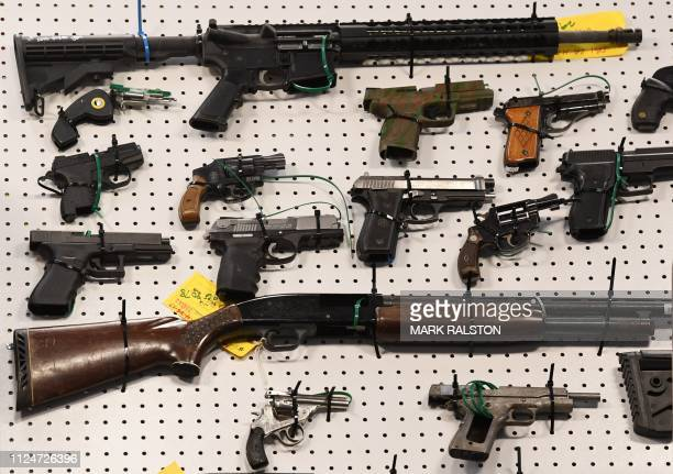 Representatives from the FBI and Los Angeles Police Department display weapons seized after a raid in which three dozen reputed members of street...
