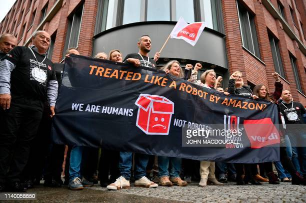 """Representatives of Amazon workers hold a banner reading """"We are Humans not robots!"""" as they demonstrate on April 29, 2019 in front of the..."""