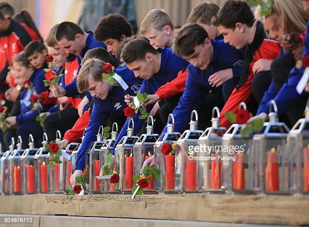Representatives of Liverpool and Everton football clubs lay a single red rose beside each of the 96 candles in memory of the victims outside...