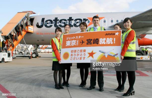 Representatives of lowcost carrier Jetstar Japan pose for photos marking the launch at Narita airport near Tokyo of its new route to Miyazaki in...