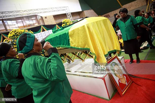 Representatives of the ANC Women's League gesture next to the coffin and the portrait of late African National Congress ward candidate Khanyisile...