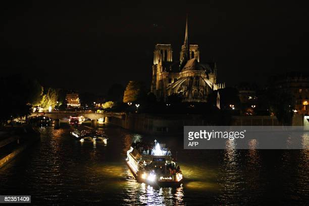 Representatives of the Catholic church tourists and followers attend a procession on fly boats as they go down the Seine river celebrating for the...