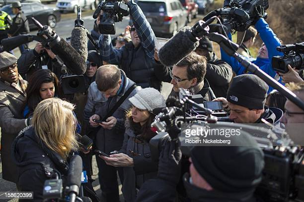 Representatives of the media interview a woman lower left who brought a bouquet of flowers December 15 2012 to a memorial near the Sandy Hook...