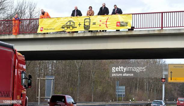 Representatives of the road patrol state government police and economy present a banner with a car a cellphone and a sad face on a highway bridge in...