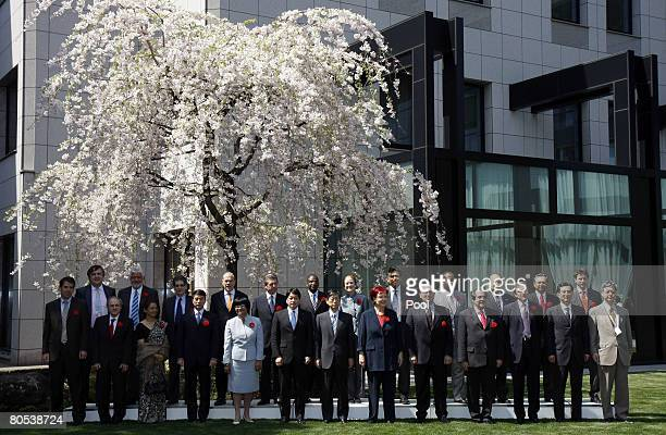 Representatives participating in the G-8 Development Ministers' Meeting pose for a group photo under cherry blossoms April 6, 2008 in Tokyo, Japan....