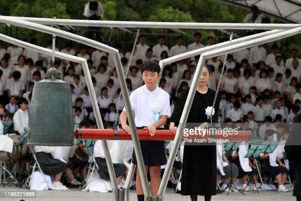 Representatives ring the Peace Bell during the Peace Memorial Ceremony on the 74th anniversary of the atomic bombing of Hiroshima at the Hiroshima...