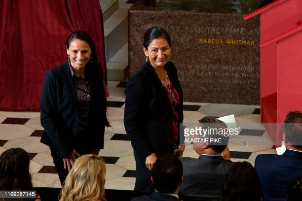 Representatives Sharice Davids and Deb Haaland stand to people clapping as they are recognized as the first Native American women elected to Congress...