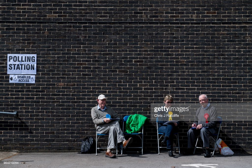 Representitives from Conservative, Liberal Democrat and Labour Parties sit outside a polling station at a school in Twickenham as voters go to the polls in the English local council elections on May 3, 2018 in London, England. Votes are being cast in more than 4,300 council areas in the biggest test for the political parties since the general election last year.