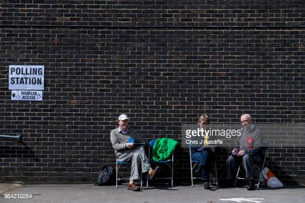 Representitives from Conservative Liberal Democrat and Labour Parties sit outside a polling station at a school in Twickenham as voters go to the...