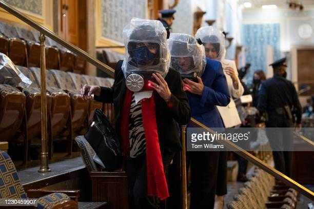 Reps. Lucille Roybal-Allard, D-Calif., and Annie Kuster, D-N.H., center, take cover as rioters attempt to break in to the joint session of Congress...