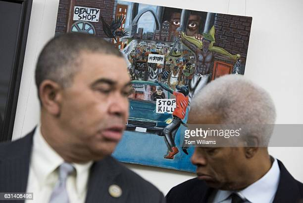 Reps William Lacy Clay DMo left and Hank Johnson DGa speak in front of the painting by Missouri high school student David Pulphus after it was rehung...